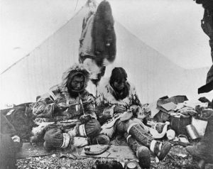 Eskimos_drilling_ivory_and_making_mukluks,_Port_Clarence,_Alaska,_ca_1900_(HEGG_337)